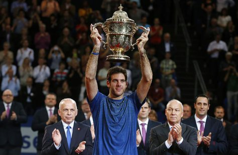 Juan Martin Del Potro (C) of Argentina raises the winner's trophy after he won his final match against Switzerland's Roger Federer at the Sw