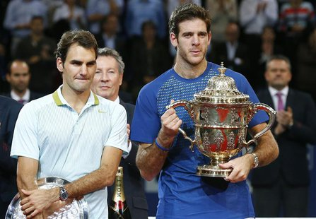 Juan Martin Del Potro (R) of Argentina poses with the winner's trophy after he won his final match against Switzerland's Roger Federer (L) a