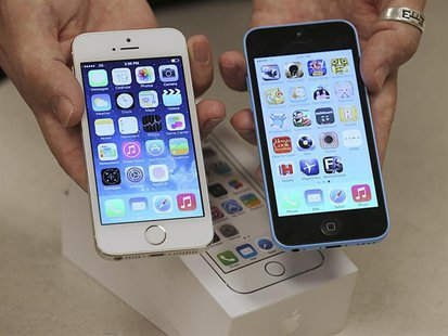 An employee shows the the front of a new Apple iPhone 5C (R) and iPhone 5 S (L) at a Verizon store in Orem, Utah September 19, 2013. REUTERS
