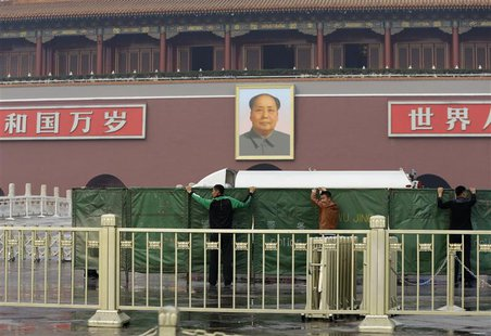 Policemen set up barriers in front of the giant portrait of the late Chinese chairman Mao Zedong as they clean up after a car accident at th