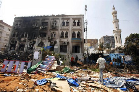 A man walks on debris outside the Rabaa Adawiya mosque complex, after the clearing of a protest camp around the mosque, in Cairo, in this fi