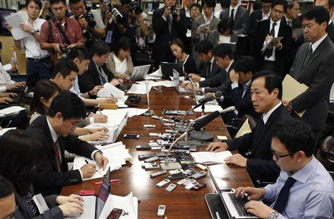 Mizuho Financial Group President Yasuhiro Sato (2nd R) attends a news conference at the Bank of Japan headquarters in Tokyo October 28, 2013