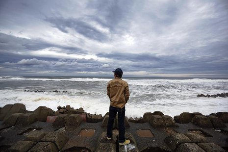 A man watches waves break into anti-tsunami barriers after a storm in Iwaki, Fukushima Prefecture September 16, 2013. REUTERS/Stringer