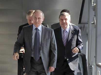 Russia's President Vladimir Putin (L) and International Olympic Committee (IOC) President Thomas Bach (R) walk during the opening of a railw