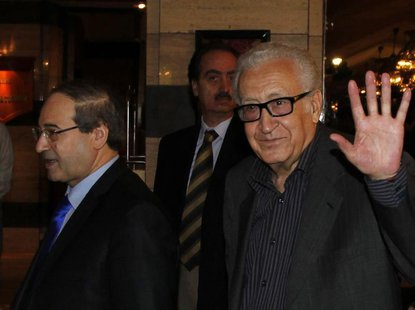 United Nations Peace Envoy for Syria Lakhdar Brahimi (R) waves to journalists during his arrival at a hotel in Damascus October 28, 2013. Se