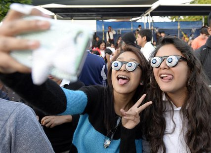Children take pictures during an attempt to break a world record for largest gathering of people wearing googly eye glasses (also know as sl