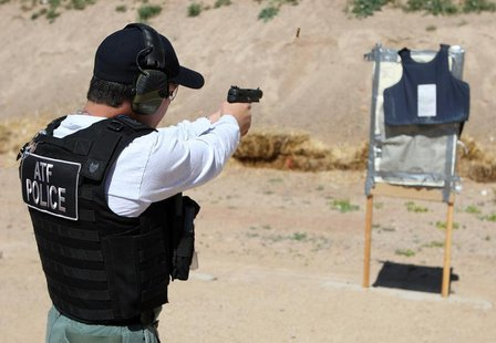 "An ATF agent fires rounds from an FN 5.7 Herstal pistol, better known on the streets as a ""Cop Killer"" weapon, at a body armor vest during a"