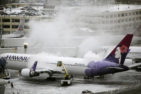 A Hawaiian Airlines plane, delayed for approximately 4 hours, undergoes de-icing before takeoff at Seattle-Tacoma International Airport in S