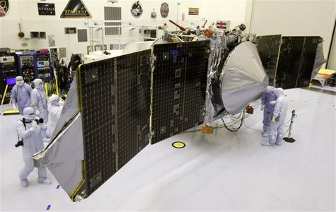 Technicians work on NASA's next Mars-bound spacecraft, the Mars Atmosphere and Volatile Evolution (MAVEN) spacecraft, as it is displayed for