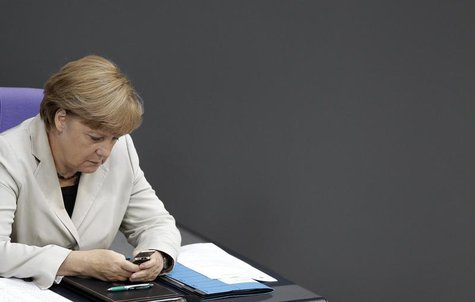 German Chancellor Angela Merkel looks at her mobile phone during a session of the Bundestag, German lower house of parliament, at the Reichs