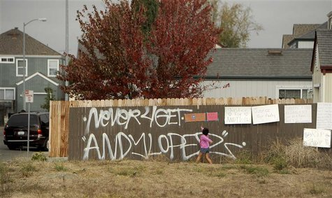 A girl reads signs in a vacant lot where 13-year-old Andy Lopez Cruz was shot and killed by sheriff's deputies on Tuesday in Santa Rosa, Cal