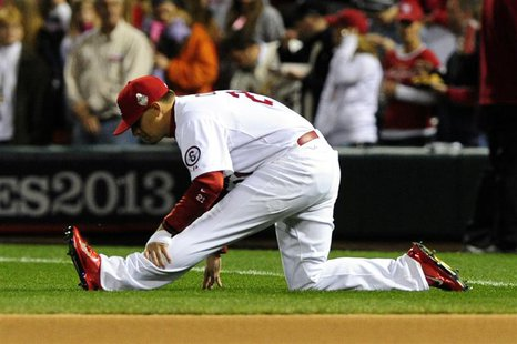 St. Louis Cardinals first baseman Allen Craig (21) stretches prior to starting at first base for game five of the MLB baseball World Series