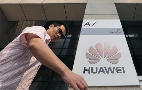 A man walks past a Huawei company logo outside the entrance of a Huawei office in Wuhan, Hubei province, October 9, 2012. REUTERS/Stringer