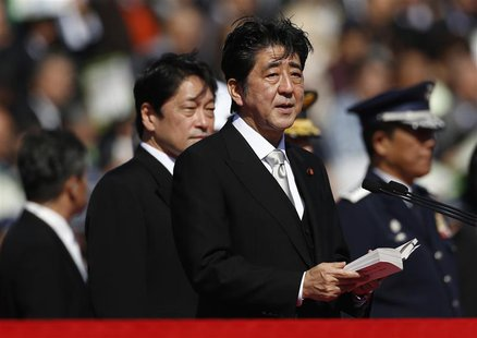 Japanese Prime Minister Shinzo Abe (C), flanked by Defence Minister Itsunori Onodera (2nd L), delivers a speech as he reviews Japan Self-Def