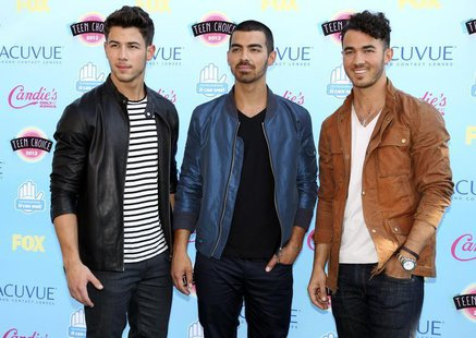 Singers (L-R) Nick, Joe and Kevin Jonas pose as they arrive at the Teen Choice Awards at the Gibson amphitheatre in Universal City, Californ