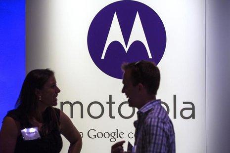 A man and woman laugh in front of a Motorola logo at a launch event for Motorola's new Moto X phone in New York, August 1, 2013. REUTERS/Luc