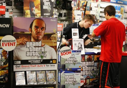 "Game enthusiasts purchase the latest release of ""Grand Theft Auto Five"" after the game went on sale at the Game Stop store in Encinitas, Cal"