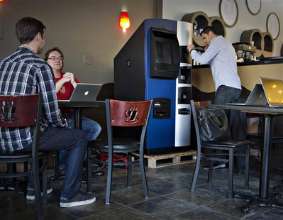 Vancouver Bitcoiniacs Trading Company co-founder Mitchell Demeter prepares, according to him, the first bitcoin ATM machine in a Waves Coffe