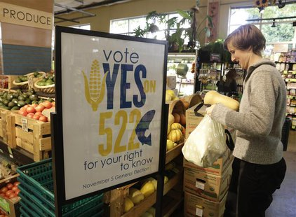 A customer picks up produce near a sign supporting a ballot initiative in Washington state that would require labelling of foods containing