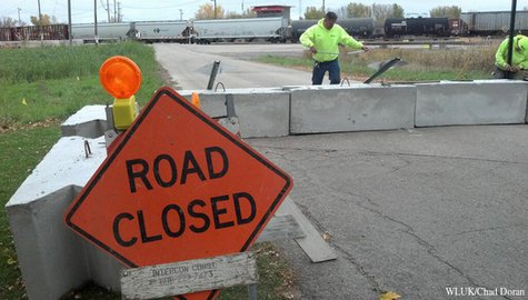 Workers place temporary barricades along a stretch of Lakeshore Dr. in North Fond du Lac, Oct. 29, 2013. The barricades are the first step in closing the road so trains do not need to blow their horns when traveling through the area. (Photo by: FOX 11).