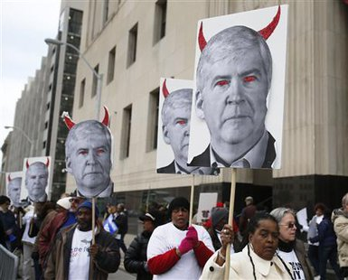 Protesters hold posters depicting Michigan Governor Rick Snyder as a devil, at a rally outside Theodore Levin U.S. Courthouse during Detroit's bankruptcy eligibility trial in Detroit, Michigan October 28, 2013. REUTERS/Rebecca Cook