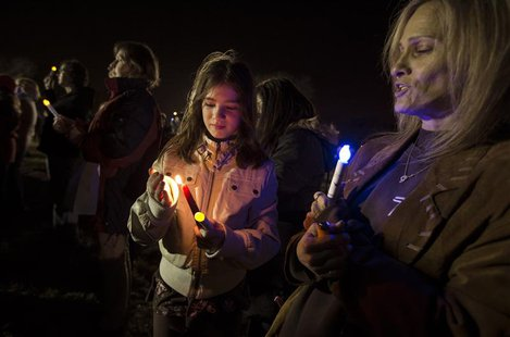 Residents of Staten Island in New York City hold lights and candles as they stand on Midland Beach on the south shore of the Island during a