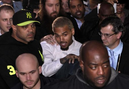 Rapper Chris Brown (C) leaves the U.S. District Court in Washington October 28, 2013. Rapper Chris Brown was due in court to face a felony a