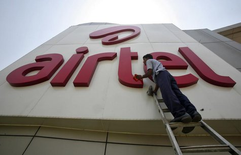 A worker cleans a logo of Bharti Airtel at its zonal office building in the northern Indian city of Chandigarh May 2, 2013. REUTERS/Ajay Ver
