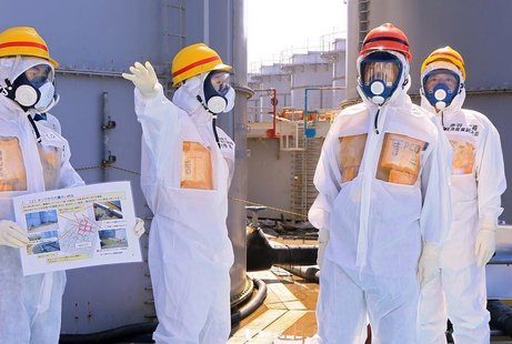 Japan's Prime Minister Shinzo Abe (2nd R), wearing protective suit and mask, is briefed about tanks containing radioactive water by Fukushim