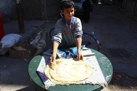 A boy makes bread in Duma neighbourhood, in Damascus September 22, 2013. All official government bakeries were closed since 10 months ago an