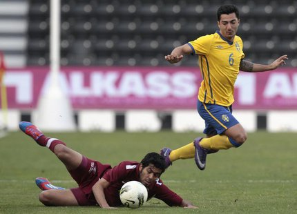 Sweden's Jiloan Hamad (R) fights for the ball with Qatar Olympic team's Mohammed AlJabri during their international friendly match in Doha J