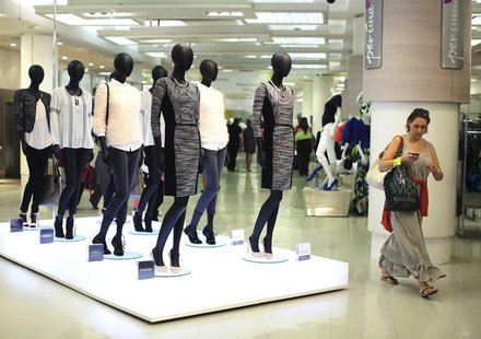 A shopper passes mannequins wearing the new autumn/ winter women's wear collection in Marks & Spencer's in central London on July 25, 2013.