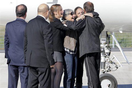 Former French hostage Daniel Larribe (R) is welcomed by relatives as French President Francois Hollande (L) and French Defence Minister Jean
