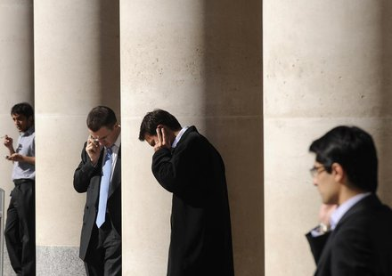 City workers make phone calls outside the London Stock Exchange in Paternoster Square in the City of London at lunchtime October 1, 2008. RE