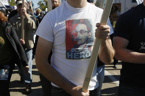 "A demonstrator wears a T-shirt depicting former U.S. spy agency contractor Edward Snowden at the ""Stop Watching Us: A Rally Against Mass Sur"