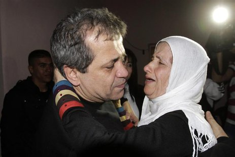 Released Palestinian prisoner Moayyad Hajji, 46, who was arrested in 1992, hugs his sister upon his arrival at his family's house in the Wes