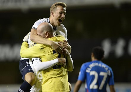 Tottenham Hotspur's Harry Kane (top) celebrates beating Hull City in a penalty shoot out with Kyle Walker and Brad Friedel (front L) during