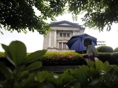 A pedestrian holding an umbrella walks past the Bank of Japan building in Tokyo June 11, 2013. REUTERS/Yuya Shino