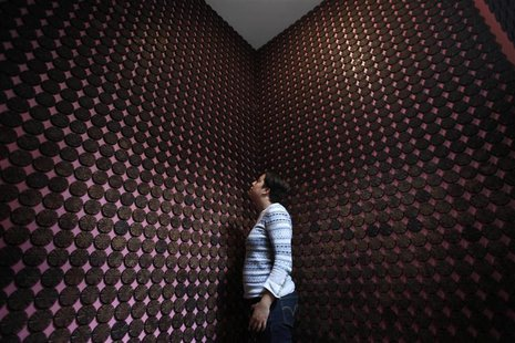 "A woman stands next to more than 2,000 chocolate samples adhered to the walls inside ""Mucho"", a chocolate museum, in Mexico City October 29,"