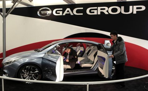 Two workers prepare GAC Motor's range-extended electric hybrid F-jet concept vehicle for display in Cobo Center in advance of media preview