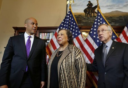 U.S. Senator-elect Cory Booker (D-NJ), and his mother, Carolyn Booker stand with U.S. Senate Majority Leader Harry Reid (L-R) before Booker