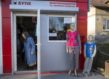 A woman leaves a shop in the small Ukrainian town of Pustomyty, near the western city Lviv October 31, 2013. REUTERS/Gleb Garanich