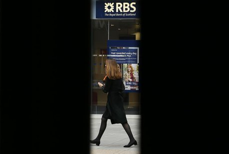 A woman is seen through scaffolding as she walks past a branch of the Royal Bank of Scotland in London September 17, 2013. REUTERS/Stefan We