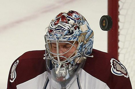 The puck goes by the mask of Colorado Avalanche's Semyon Varlamov from a shot by the Chicago Blackhawks during the second period of their NH