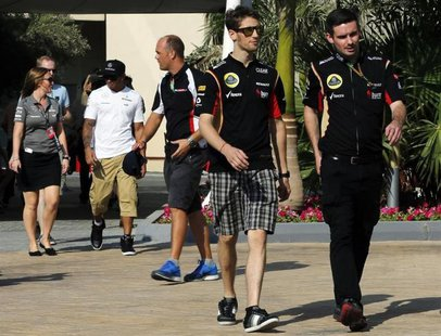 Lotus Formula One driver Romain Grosjean of France (L) arrives at a news conference ahead of the Abu Dhabi F1 Grand Prix at the Yas Marina c