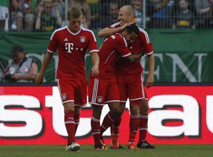 Bayern Munich's Thiago of Spain (C) celebrates his goal against Borussia Moenchengladbach with Arjen Robben (R) and Toni Kroos during their
