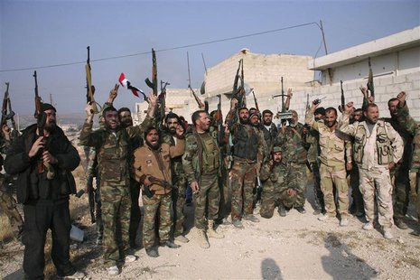 Forces loyal to Syria's President Bashar al-Assad hold up their weapons as they cheer in the town of Safira November 1, 2013. REUTERS/George