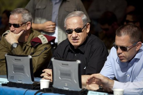 Israeli Prime Minister Benjamin Netanyahu (C) sits next to armed forces chief Major-General Benny Gantz (L) and Gilad Erdan, minister of com
