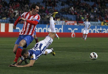 Atletico Madrid's Diego Godin (L) and Espanyol's Simao Sabrosa fight for the ball during their Spanish first division soccer match at Vicent