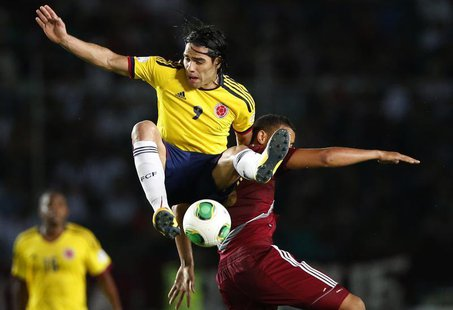 Colombia's Radamel Falcao Garcia (9) challenges Venezuela's Tomas Rincon during their 2014 World Cup qualifying soccer match in Puerto Ordaz